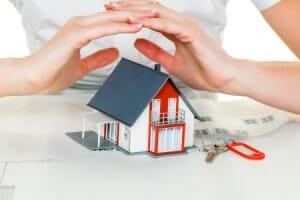 Sicherheitsberatung - eine Frau hält schützend ihre Hände über ein (Modell-)Haus
