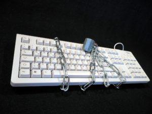 Mit unseren Tipps können Sie sich leicht ein Passwort merken. Zu sehen ist eine Tastatur, die mit einem Schloss umwickelt ist.